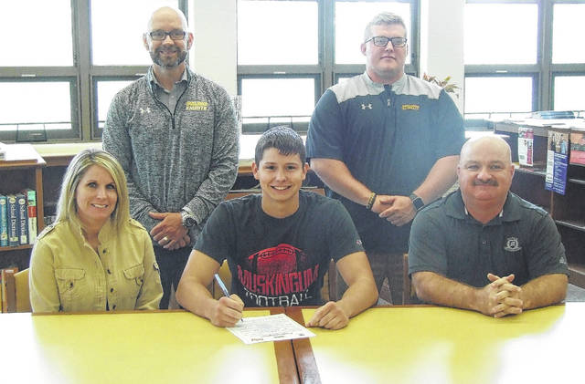 Nate Hall signs his letter of intent to play football for Muskingum University. Flanking Hall in the front row are his mother, Amy Marshall, and grandfather, Chuck Harris. In the back row are (l-r): Northmor principal Benjamin Bethea and assistant football coach Spenser Whisler.