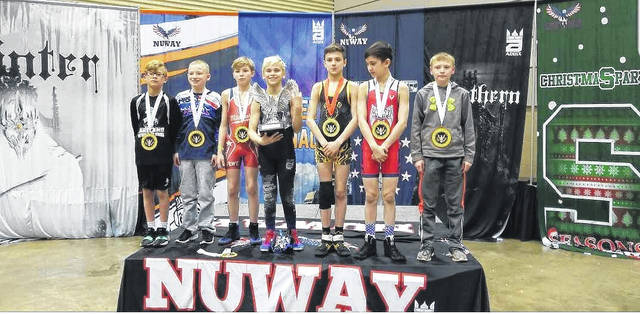 Submitted photo Aydan Reyes (center) poses and smiles with his hardware after wrestling his way to his third consecutive NUWAY National Championship.
